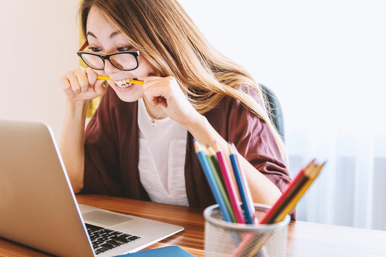 Frau sitzt vor Laptop und beißt auf einen Stift