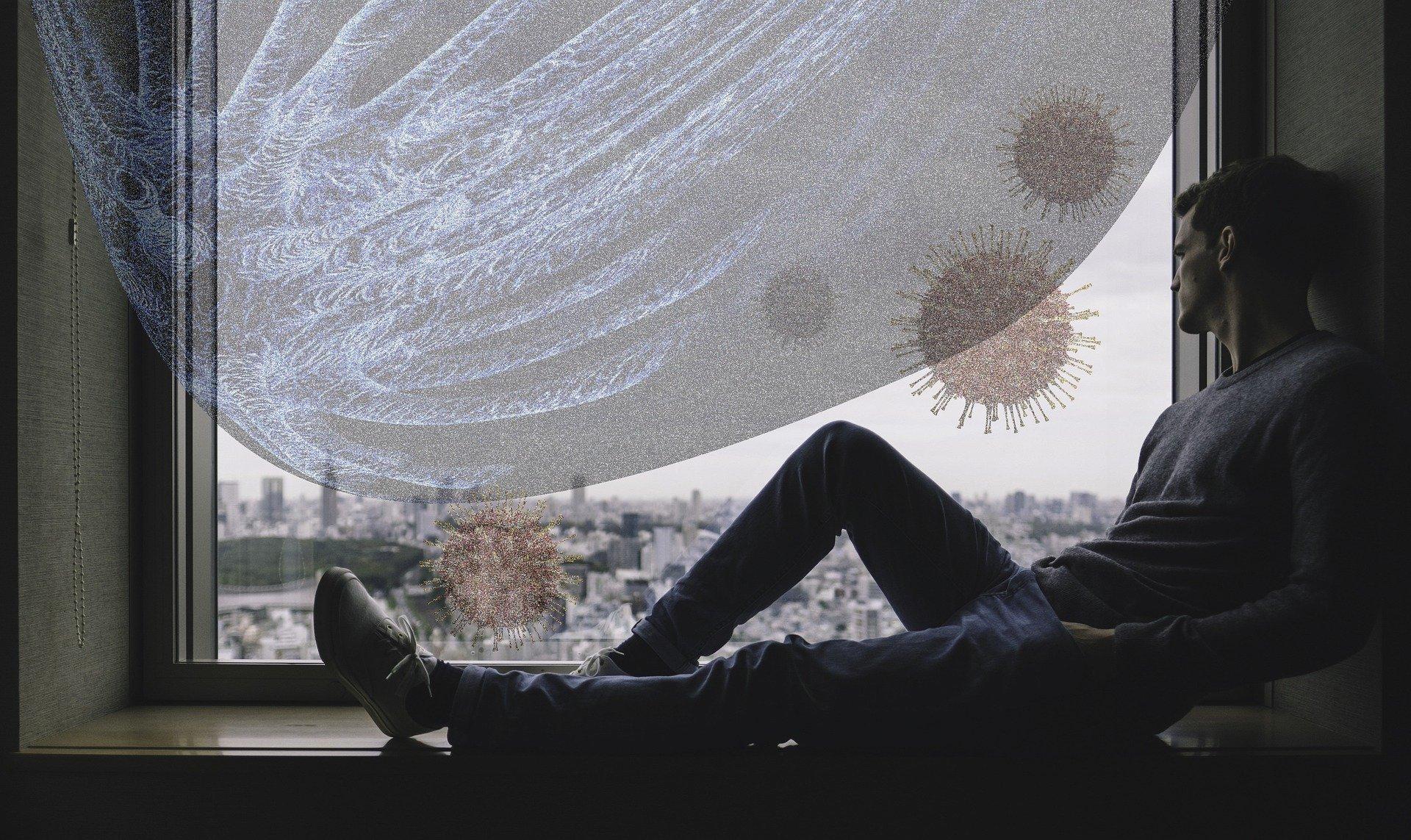 Sitzender Mann am Fenster und schaut auf Coronaviren